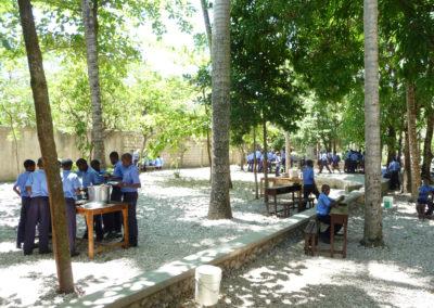 Les élèves prennent le repas de midi pendant qu'Haïti Futur installe le TNI dans l'école,.